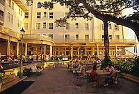 Local musicians perform on the Sheraton Moana Surfrider Hotel lanai, with people relaxing during the sunset in Waikiki