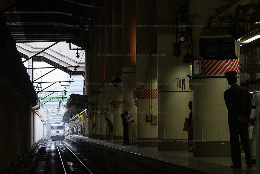 A train guard waits for an approaching train at Ueno station, Tokyo, Japan Saturday, October 11th 2008