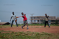 Jonathan Kizza, 11, hits the ball during evening softball game at sports field of St. Peter's School in Nsambya, neighbourhood of Kampala, Uganda on July 28 2011. Jonathan Kizza plays 2nd base on Rev. John Foundation Little League baseball team.