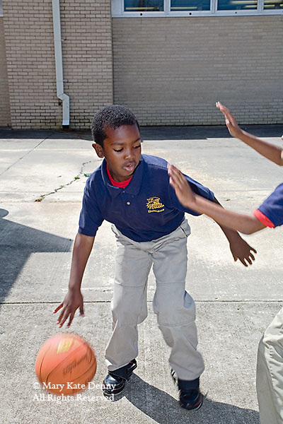 African American seven year old male in school uniform dribbles basketball and.arm of other boy reaches out to guard at Louisiana school.