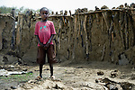 A boy stands in front of the wall of a burned hut in Leu, a village in the contested Abyei region along the border between Sudan and South Sudan. The village was looted and burned in 2011 when soldiers and militias from the northern Republic of Sudan swept through the area, chasing out more than 100,000 Dinka Ngok residents. A few thousand families have returned to the region since northern combatants withdrew in 2012, yet their life is precarious. In Leu, the Catholic Church rehabilitated a clinic and drilled a well. For political and logistical reasons, the Catholic Church is one of the few organizations willing to openly accompany the people of Abyei during these uncertain times.