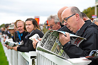 A race goer studies The Racing Post on the rails during Bathwick Tyres Reduced Admission Race Day at Salisbury Racecourse on 9th October 2017