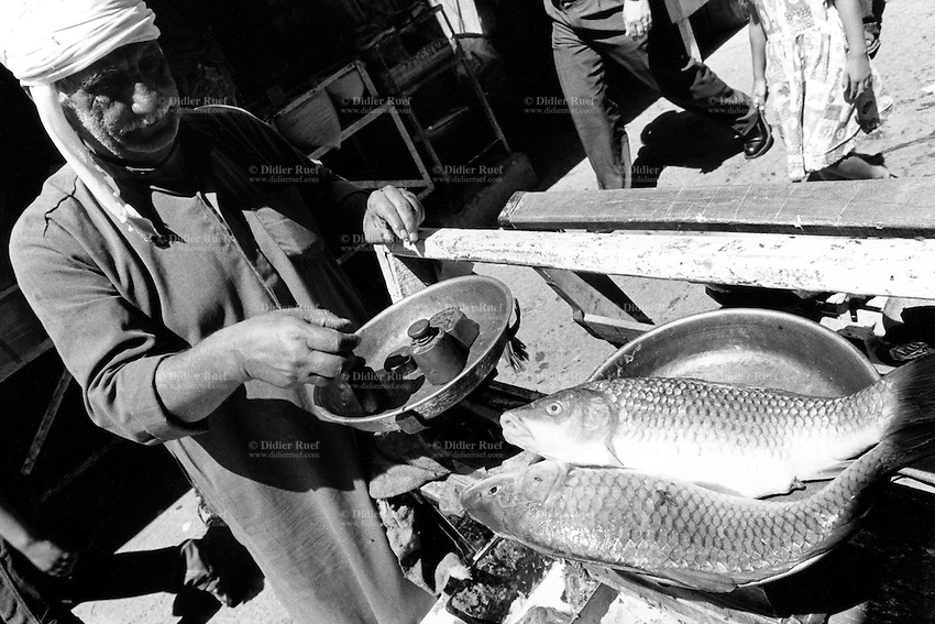 Iraq. Baghdad. An old man sells fish in an open air market.                                                                          Fish being weighed on scale. © 2003 Didier Ruef