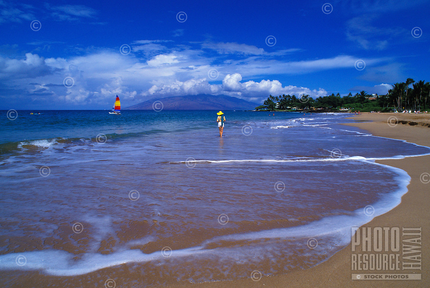 A woman enjoys a stroll along Wailea Beach in front of the Wailea Marriott and the Grand Wailea Resort. The West Maui Mountains can be seen in the background. One of Maui's best beaches, it is popular for walking, snorkeling and more.