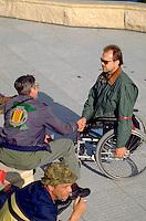 Legless wheelchair veteran age 55 shaking hands at Minnesota Vietnam Memorial Wall.  St Paul  Minnesota USA