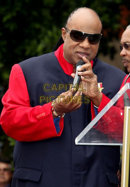 Stevie Wonder.Shotgun Tom Kelly honored with a star on the Hollywood Walk of Fame held at TCL Chinese Theatre, Hollywood, California, USA..April 30th, 2013.half length black blue jacket red sleeves sunglasses shades microphone .CAP/ADM/RE.©Russ Elliot/AdMedia/Capital Pictures.