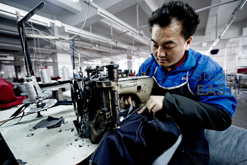 Textile worker LONG Zhaoxing sews blue jeans in LSH textile company, in Xintang, Guangdong province, China, on February 9, 2012. Photo by Lucas Schifres/Pictobank