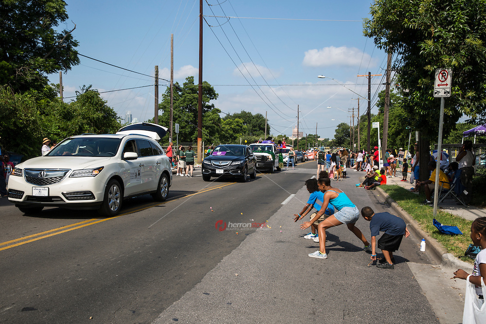 AUSTIN, TEXAS - Children race to pick up candy off the street thrown by parade floats at the 2016 Central Texas Juneteenth Celebration Parade in East Austin, Texas.<br /> <br /> Juneteenth marks the anniversary of June 19, 1865, the day slaves in Texas learned they were free, two years after President Abraham Lincoln signed the Emancipation Proclamation.<br /> <br /> Use of this image in advertising or for promotional purposes is prohibited.<br /> <br /> Editorial Credit: Dan Herron / Herronstock Editorial.
