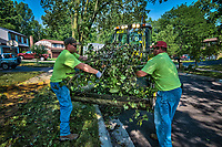 A pair of city workers in Westerville, Ohio, load tree debris into a front-end loader for transport to a waiting dump truck three days after a storm felled trees and power lines leaving as many as 1 million people without power in Ohio. City crews worked extended 12-hour days to begin clearing fallen trees from city property and debris placed in the berm near city roads.