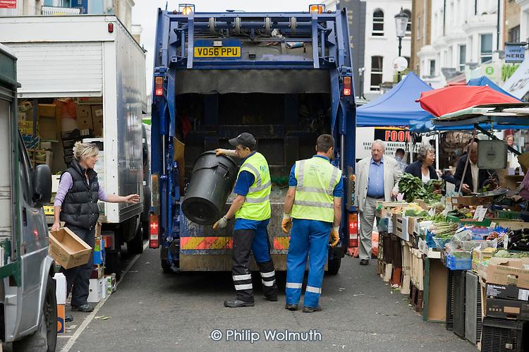 Dustmen employed by contractor SITA clear market refuse in Portobello Road, Kensington & Chelsea, London.