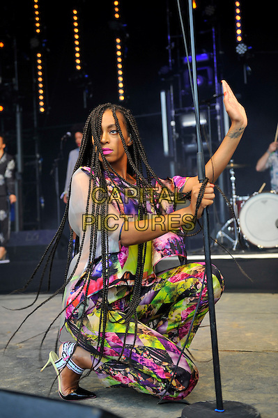 Solange (Solange Knowles) <br /> performing at Glastonbury Festival, Worthy Farm, Pilton, Somerset, <br /> England, UK, 28th June 2013.<br /> half length music gig concert gig live on stage singing long hair braids  kneeling down profile hand pink yellow white print catsuit jumpsuit top trousers matching side <br /> CAP/MAR<br /> &copy; Martin Harris/Capital Pictures