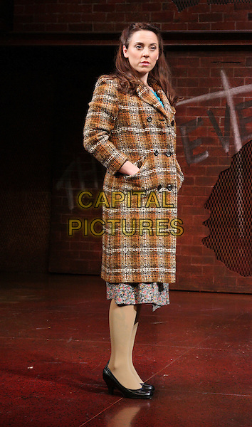 "MELANIE CHISHOLM (Mel C) as Mrs Johnston .""Blood Brothers"" photocall, Phoenix Theatre, London, England. .October 21st 2009.sporty spice scene stage acting full length brown yellow orange tweed coat jacket black shoes hands in pockets.CAP/ROS.©Steve Ross/Capital Pictures."