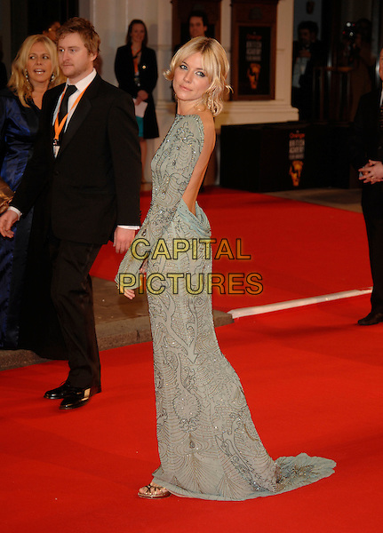 SIENNA MILLER.Red Carpet Arrivals at The Orange British Academy Film Awards (BAFTA's) held at the Royal Opera House, Covent Garden, London, England, February 11th 2007..full length grey gold beaded long sleeved dress back behind .CAP/PL.©Phil Loftus/Capital Pictures