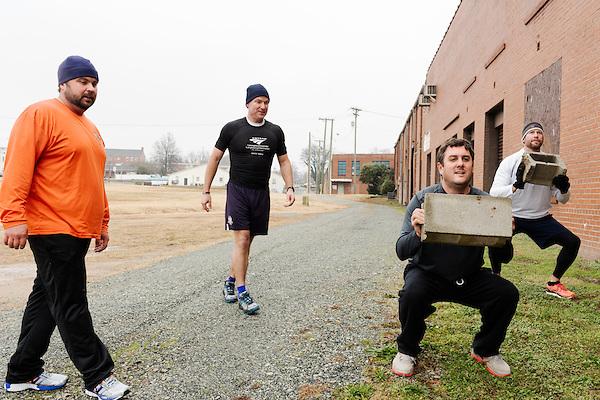December 22, 2014. Lexington, North Carolina.<br />  (right to left) Geoff Gardner and Frank Callicutt lift cinder blocks as Mayor Newell Clark, center, and Dale Calhoun look on.<br />   Newell Clark, the 43 year old mayor of Lexington, NC, leads a group of friends and colleagues on a 4 times a week exercise routine around downtown. The group uses existing infrastructure, such as an abandoned furniture factory, loading docks, stairs, and handrails to get fit and increase awareness of healthy lifestyles in a town more known for BBQ.<br /> Jeremy M. Lange for the Wall Street Journal<br /> Workout_Clark