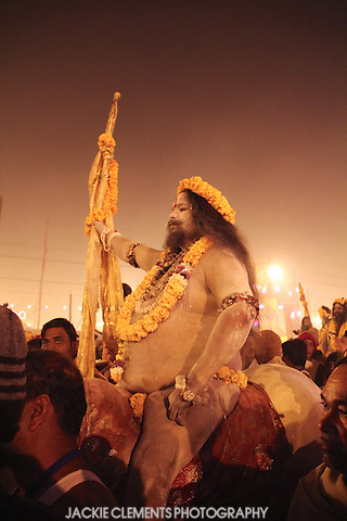 A large Naga sadhu decorated with garlands of marigolds sits on a horse, ready to take part in a pre-dawn parade to the banks of holy rivers at Prayag.