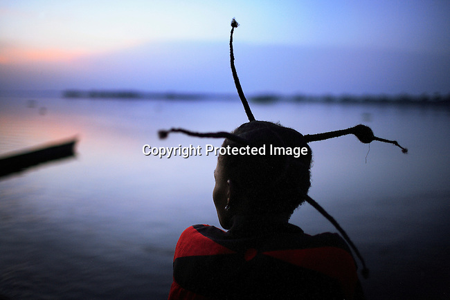 LUKUTU, DEMOCRATIC REPUBLIC OF CONGO MARCH 21: An unidentified woman looks out on the Congo River as the sun sets on March 21, 2006 in Lukutu, Congo, DRC. She is one of about five hundred people traveling on a boat from Kisangani to Kinshasa, a journey of about 1750 kilometers. The boat stopped in the village for about a week. Lukutu, located along the Congo River, is a small village with a palm oil factory and an economy of agriculture and fishing. Congo River is a lifeline for millions of people, who depend on it for transport and trade. During the Mobuto era, big boats run by the state company ONATRA dominated the traffic on the river. These boats had cabins and restaurants etc. All the boats are now private and are mainly barges that transport goods. The crews sell tickets to passengers who travel in very bad conditions, mixing passengers with animals, goods and only about two toilets for five hundred passengers. The conditions on the boats often resemble conditions in a refugee camp. Congo is planning to hold general elections by July 2006, the first democratic elections in forty years.<br /> (Photo by Per-Anders Pettersson)
