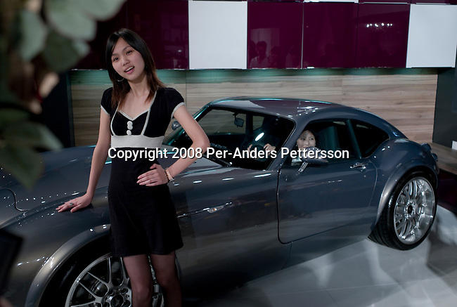SHANGHAI, CHINA OCTOBER 12: An affluent young Chinese woman poses next to a sports car at the yearly Millionaires Fair on October 12, 2008 in Shanghai, China. About fifty exhibitors showed their luxury goods such as jewelry, cars, property, kitchens and many other must haves for the newly rich. China has a growing number of millionaires and about 320,000 of them are estimated to live in Mainland China. The Chinese are currently the third-largest consumer of luxury goods, behind Japan and the United States. (Photo by Per-Anders Pettersson/Getty Images)...