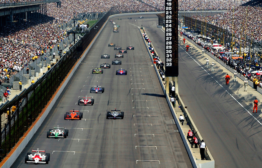 Sam Hornish leads a string of cars down the front stretch during the 2006 Indianapolis 500. Hornish would pass Marco Andretti on the last lap to win the race.<br />
