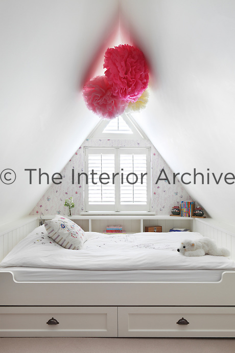 A bed with an integrated shelf has been built into the sharply sloped space of this attic bedroom