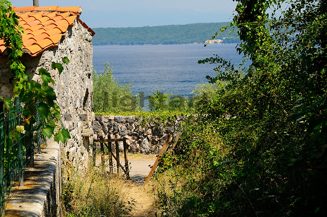 Garden door, Gartentor, old house, altes Haus, Porat, Krk Island, Dalmatia, Croatia. Insel Krk, Dalmatien, Kroatien. Krk is a Croatian island in the northern Adriatic Sea, located near Rijeka in the Bay of Kvarner and part of the Primorje-Gorski Kotar county. Krk ist mit 405,22 qkm nach Cres die zweitgroesste Insel in der Adria. Sie gehoert zu Kroatien und liegt in der Kvarner-Bucht suedoestlich von Rijeka.