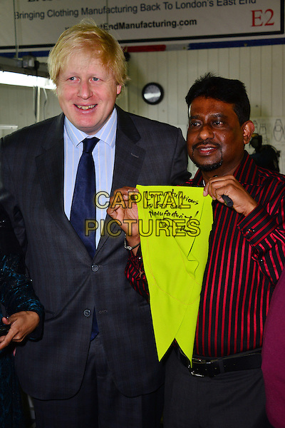 Boris Johnson & Mr. Sharif Uddin.visits newly established clothes manufacturer in East London, East End Manufacturing Ltd., London, England..26th February 2013.half length blue shirt grey gray tie suit congratulations to  yellow green neon fluorescent red stripe shirt glasses smiling .CAP/BF.©Bob Fidgeon/Capital Pictures.