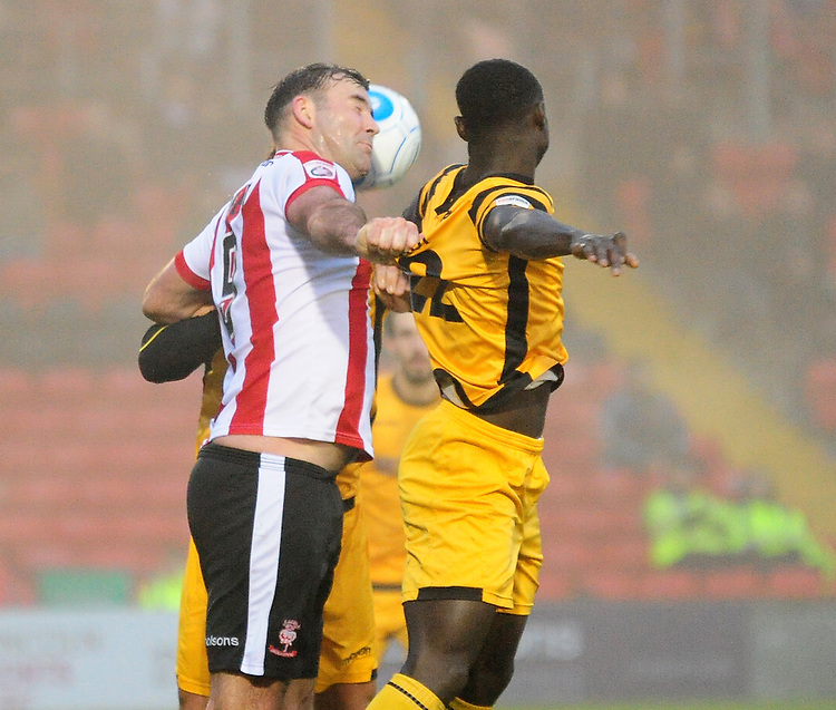 Lincoln City's Matt Rhead vies for possession with Maidstone United's Nana Ofori-Twumasi<br /> <br /> Photographer Andrew Vaughan/CameraSport<br /> <br /> Vanarama National League - Lincoln City v Maidstone - Saturday 26th November 2016 - Sincil Bank - Lincoln<br /> <br /> World Copyright &copy; 2016 CameraSport. All rights reserved. 43 Linden Ave. Countesthorpe. Leicester. England. LE8 5PG - Tel: +44 (0) 116 277 4147 - admin@camerasport.com - www.camerasport.com