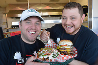 Greg, left, and Chris Skillas with a custom triple hamburger with feta fries.