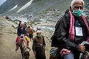 Hindu pilgrims with the help of Kashmiri guides with their ponies make their pilgrimage to Amarnath in Jammu and Kashmir, India. Hindu pilgrims brave sub zero temperature and high latitude passes and make their pilgrimage to reach the sacred Amarnath cave, which houses a lingam - a stylized phallus, worshiped by Hindus as a symbol of God Shiva. Photo: Sanjit Das/Panos
