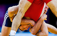 11 DEC 2011 - LONDON, GBR -  Adam Sobieraj (POL) (in blue) tries to overpower Oleg Motsalin (GRE) (in red) during their 74kg category quarter final bout during the London International Wrestling Invitational and 2012 Olympic Games test event  at the ExCel Exhibition Centre in London, Great Britain (PHOTO (C) NIGEL FARROW)