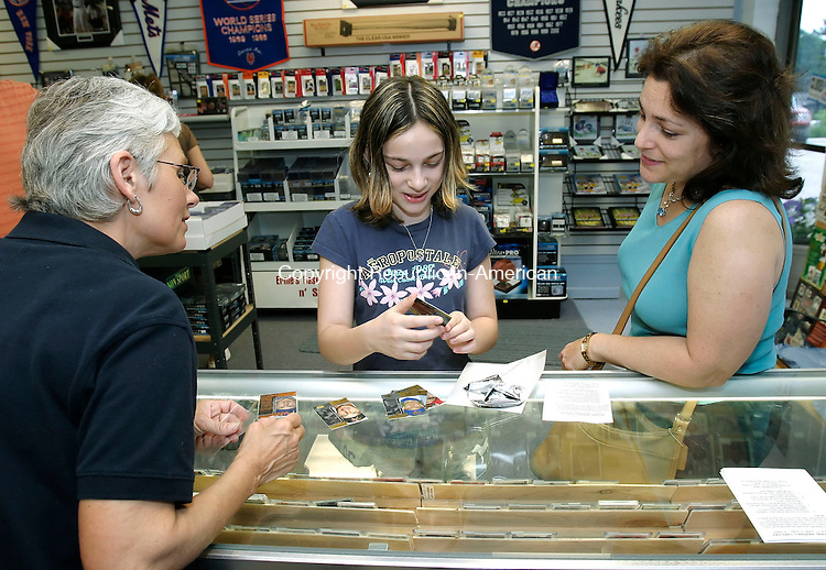 SEYMOUR, CT, 14 June 2006- 061406BZ01-  First-time card buyer Shana Konoval, 11, of Oxford, center, gets help from Sandy Thompson, co-owner of Ernie's Baseball Cards in Seymour, left, and her mother Judy Konoval, right,  while sorting through a pack of Topps Co-Signers cards Wednesday night. Shana, who was rewarded with the cards for getting good grades in school, got a Mickey Mantle number card and a limited edition, #113/150 Paul LoDuca card in the pack.<br /> Jamison C. Bazinet Republican-American