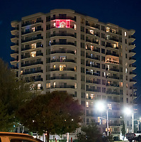 An LED light display of the Canadian flag shines through the night on the 14th floor of the Waters Edge apartment building on Front Street.