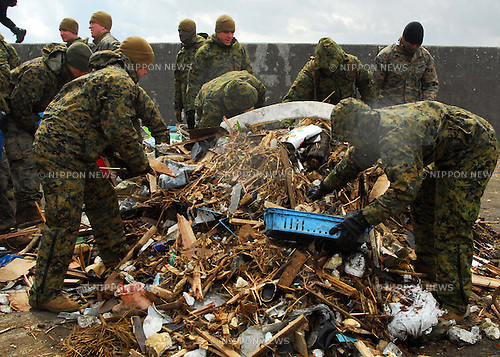 OSHIMA, Japan (April 4, 2011) Marines assigned to the 31st Marine Expeditionary Unit (31st MEU) pick up debris on Oshima, as part of ongoing disaster relief efforts. Marines and Sailors with the 31st MEU are on Oshima Island to help clear a harbor and assist with cleaning debris from roads and a local school in support of Operation Tomodachi. (Photo by U.S. Navy/AFLO) [0006]