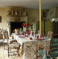A length of fabric, also used for upholstering the chairs, doubles as a tablecloth in this French dining room