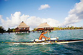 FRENCH POLYNESIA, Tahaa Island. Roe, riding his outrigger canoe by the Vahine Private Island Resort.