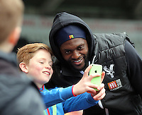 Emmanuel Adebayor of Crystal Palace poses for a selfie with a young fan arrives before the Barclays Premier League match between Swansea City and Crystal Palace at the Liberty Stadium, Swansea on February 06 2016