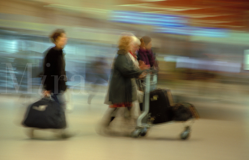 Passengers taking their baggage to check-in at busy airport.