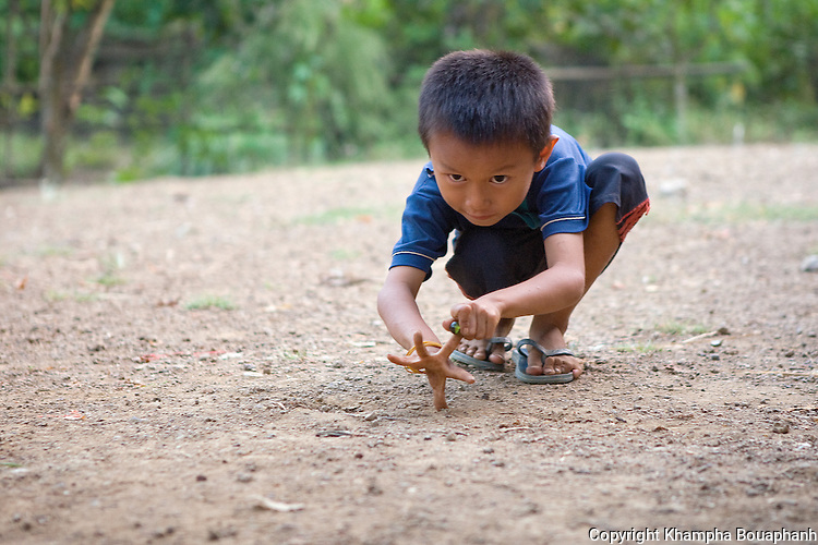 A local boy plays marble at a village near Vang Vieng, Laos on November 4, 2009.   (Photo by Khampha Bouaphanh)
