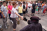 Street Performer entertains a crowd that has gathered.  Boy shakes had approvingly after giving a tip