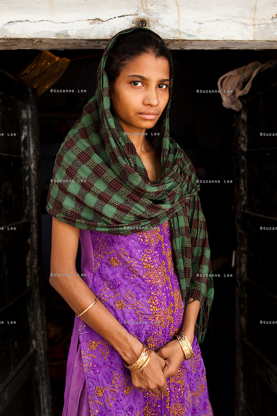Sadma Khan, 19, poses for a portrait at the door of her mother's one-room house in a slum area of Tonk, Rajasthan, India, on 19th June 2012. She was married at 17 years old to Waseem Khan, also underaged at the time of their wedding. The couple have an 18 month old baby and Sadma is now 3 months pregnant with her 2nd child and plans to use contraceptives after this pregnancy. She lives with her mother since Waseem works in another district and she can't take care of her children on her own. Photo by Suzanne Lee for Save The Children UK