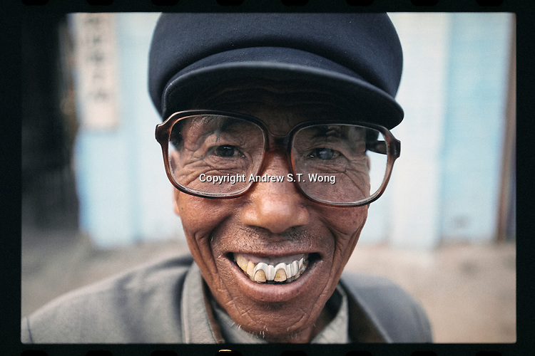 A poor Chinese peasant flashes his false teeth as he beams at a market in Lanxian county in northern Shanxi province, China, September 1998. Lanxian, on the Loess Plateau, was one of the poorest counties in China with most of the residents living under the poverty line earning less than US$ 100 per person each year.
