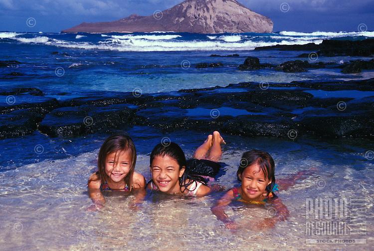 Kids playing in tidepool at Makapuu Beach Park, on Oahu's eastern coast. Rabbit island is in the background.