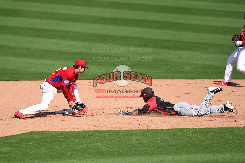 Philadelphia Phillies infielder Chase d'Arnaud (62) takes a throw as Giovanny Alfonzo (2) slides in during an exhibition game against the University of Tampa on March 1, 2015 at Bright House Field in Clearwater, Florida.  University of Tampa defeated Philadelphia 6-2.  (Mike Janes/Four Seam Images)