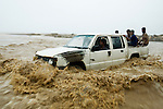 Teenager driving pickup truck on flooded road during heavy rain storm, Hawf Protected Area, Yemen