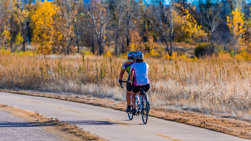 Couple on a tandem bike riding along the extensive bike trail system in Littleton, Colorado USA.