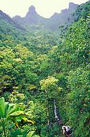Couple treks below eroded peaks on the verdant Kalalau Trail, Kauai