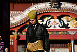 """A staffer wearing traditional garb stands in front of Houshinmon Gate inside the grounds of Shuri-jo Castle in Naha, Okinawa Prefecture, Japan, on June 24, 2012. Houshomon is the final gate leading to the main """"Seiden"""" hall, a detail of which can be seen in the background. Photographer: Robert Gilhooly"""