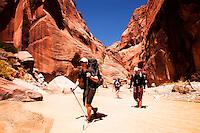 Hikers wade down the Paria River in southern Utah.