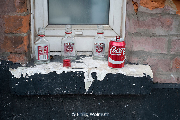 Empty Smirnoff bottles left by street drinkers on a window ledge in north London.