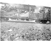 Side view of badily wrecked box car with no siding or other identification.<br /> D&amp;RGW