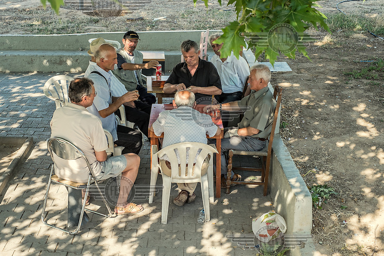 ATHENS, GREECE: a group of retired men play domino in a park.